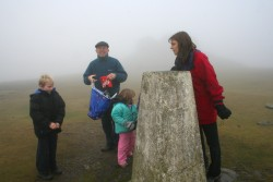 Carolyn and Co. inspect the trig point